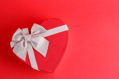 Gift box in the shape of a heart with a ribbon on a red background. The concept is suitable for love stories, birthdays and Valent. Ine`s Day royalty free stock images