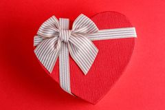 Gift box in the shape of a heart with a ribbon on a red background. The concept is suitable for love stories, birthdays and Valent. Ine`s Day stock image