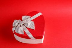 Gift box in the shape of a heart with a ribbon on a red background. The concept is suitable for love stories, birthdays and Valent. Ine`s Day royalty free stock image