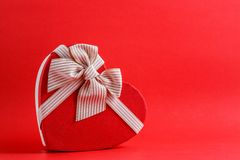 Gift box in the shape of a heart with a ribbon on a red background. The concept is suitable for love stories, birthdays and Valent. Ine`s Day royalty free stock photo