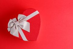 Gift box in the shape of a heart with a ribbon on a red background. The concept is suitable for love stories, birthdays and Valent. Ine`s Day royalty free stock photography