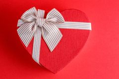 Gift box in the shape of a heart with a ribbon on a red background. The concept is suitable for love stories, birthdays and Valent. Ine`s Day stock photography