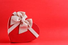 Gift box in the shape of a heart with a ribbon on a red background. The concept is suitable for love stories, birthdays and Valent. Ine`s Day stock images
