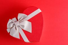Gift box in the shape of a heart with a ribbon on a red background. The concept is suitable for love stories, birthdays and Valent. Ine`s Day stock photos