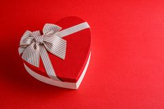 Gift box in the shape of a heart with a ribbon on a red background. The concept is suitable for love stories, birthdays and Valent. Ine`s Day stock photo