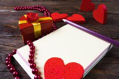 Gift box in the shape of a heart tied with a gold ribbon and surrounded by decorative hearts . royalty free stock photos
