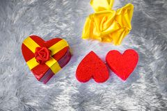 Gift box in the shape of a heart tied with a yellow ribbon with a bow in the shape of a rose lies on the pillow fake fur and next Stock Images