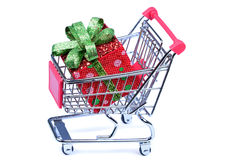 Gift box in a shopping cart on white background Stock Photos