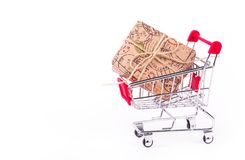 Gift box in shopping cart on white background. Shop trolley. Discounts and gifts. Copy space stock images