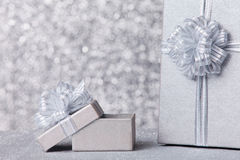 Gift box with silver ribbon, glittery silver background Royalty Free Stock Photography