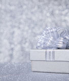 Gift box with silver ribbon, glittery silver background Stock Images