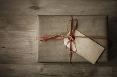 Gift Box with Simple Wrapping and Grungy Parcel Tag Stock Photo
