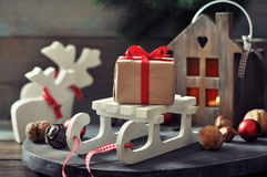 Gift box on sled. Christmas decorations with gift box on sled and  lantern on wooden background Royalty Free Stock Photography