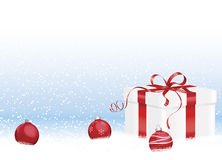 Gift Box in Snow with Ornaments Royalty Free Stock Photo