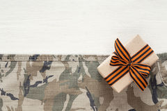 Gift box with st george ribbons on the khaki background. Defender of the Fatherland Day. Space for text stock image