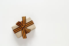 Gift box with st george ribbons on the white background. Defender of the Fatherland Day. Space for text royalty free stock photo