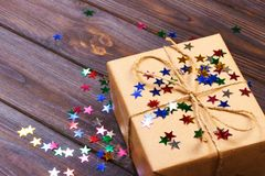 Gift box with star. Creative concept with festive decor on black background. Confetti stars, red, yellow with gift box. Explosion Stock Photography