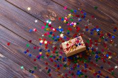 Gift box with star. Creative concept with festive decor on black background. Confetti stars, red, yellow with gift box. Explosion Stock Photos