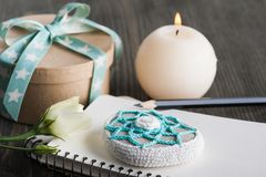 Gift box with star ribbon on dark rustic table. Gift box with star ribbon, blank note book, crochet paperweight on dark rustic table. Greeting card with heart Royalty Free Stock Photography