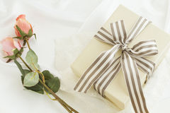 Gift box with stripe bow and roses. Gift box with stripe ribbon and pink roses Stock Photography
