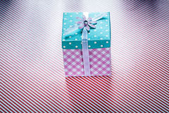 Gift box on striped fabric background top view celebrations conc Royalty Free Stock Images