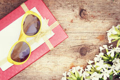Gift box and sunglasses lie on wooden background Stock Image
