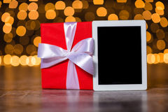 Gift box and tablet computer standing on the floor Stock Images