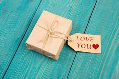 Gift box and tag with text & x22;LOVE YOU& x22;, sign in the shape of heart Stock Image