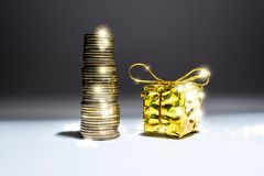 A gift box, tied with a beautiful golden bow next to a pile of gold coins with sunny, fabulous highlights on dark background. stock images