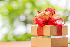 Gift box tied with gold and red ribbon. Stock Photos
