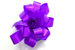 Gift box tied with a purple ribbon bow on white background. Royalty Free Stock Photography