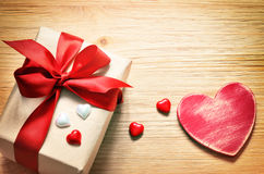Gift box tied red ribbon. Old wooden background. Stock Photos