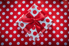 Gift box with tied ribbon on polka-dot red tablecloth celebratio Stock Image