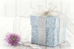 Gift box tied up with white ribbon and pink flower. Light blue floral gift box tied up with white ribbon and pink flower on rustic wooden background and texured Stock Images