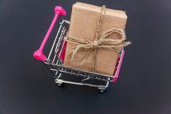 Gift box in toy cart. Mini shopping cart with vintage rustic gift box. Black background with copy space Stock Image