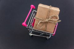 Gift box in toy cart. Mini shopping cart with vintage rustic gift box. Black background with copy space Stock Photography