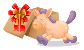 A gift box beside a toy horse Royalty Free Stock Image
