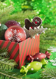 Gift box with toys and baubles on green background Stock Image