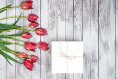 Gift box and tulips bouquet on shabby white wooden background. Space for text. Top view. Royalty Free Stock Image