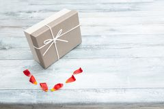 Gift box and tulips petals with place for your text on rustic b royalty free stock photography