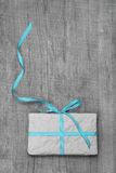 Gift box with turquoise striped ribbon on a wooden background Royalty Free Stock Photo