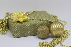 Gift box and two Christmas balls on a light background Stock Image