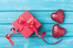 Gift box and two red heart on turquoise wooden background top view. Saint valentine day greeting card. Stock Photo