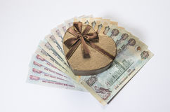 A gift box and uae currency. A heart shaped gift box on UAE Dirham currency notes Stock Image