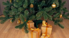 Gift box under green christmas fir tree. Brown gift box stands at floor. Christmas eve celebration holiday. Family. Presents. Time lapse close up locked down stock video footage