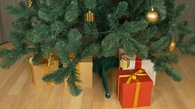 Gift box under green christmas fir tree. Red white brown gift box stands at floor. Christmas eve celebration holiday. Family Presents. Time lapse close up stock footage