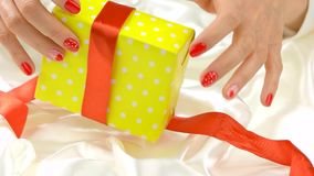 Gift box unpacking, slow motion. Young woman hands with red festive manicure opening yellow gift box on white silk. Romantic holiday concept stock footage