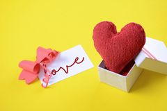 Gift box with valentines day card. Gift box with red heart and valentines day card. Love concept. Yellow background Royalty Free Stock Image