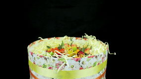 Gift box with a variety of flowers tied with a ribbon rotates stock video