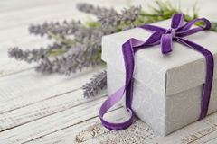 Gift box with violet ribbon. And bouquet of lavender on wooden background Royalty Free Stock Photography